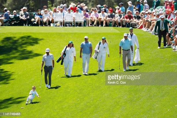 Dustin Johnson Brooks Koepka and Mark O'Meara of the United States walk with their families during the Par 3 Contest prior to the Masters at Augusta...
