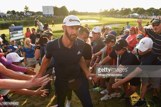 Dustin Johnson celebrates his winning putt on the 18th hole by greeting fans Adam Scott of Australia Harris English exits the course during the final...
