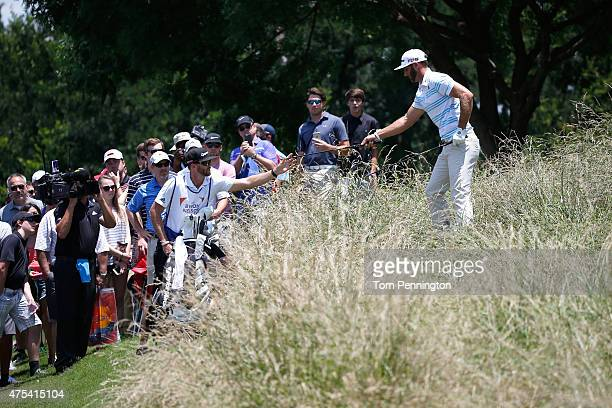 Dustin Johnson changes clubs after failing to hit the ball out of the grass on the sixth hole during the Final Round of the ATT Byron Nelson at the...