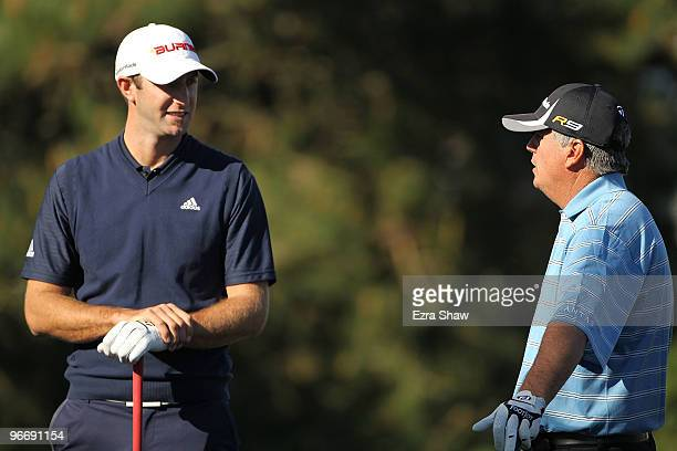 Dustin Johnson chats with playing partner Paul Goydos while waiting to tee off on the second hole during the final round of the ATT Pebble Beach...