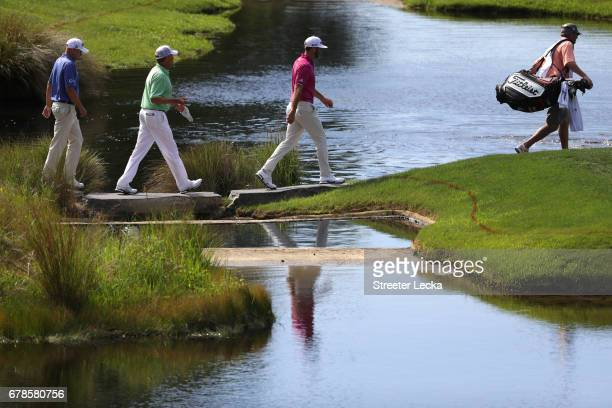 Dustin Johnson Davis Love III and Bill Haas walk on the 17th hole during round one of the Wells Fargo Championship at Eagle Point Golf Club on May 4...