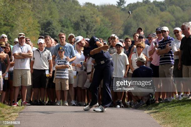 Dustin Johnson hits a shot off of the cart path along the seventh hole as the gallery watches during the second round of the Deutsche Bank...