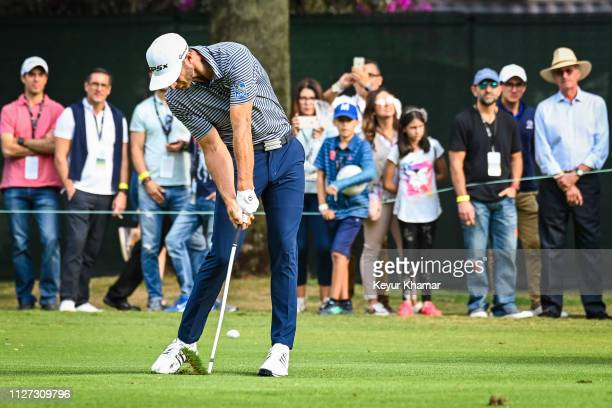 Dustin Johnson makes impact as he plays a shot on the 16th hole fairway during the final round of the World Golf Championships Mexico Championship at...