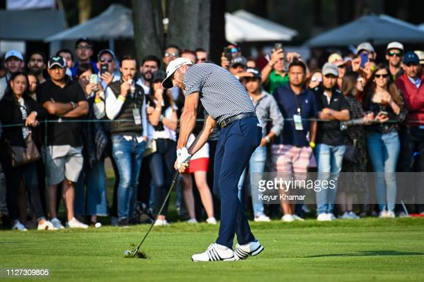 Dustin Johnson makes impact with his second shot on the 18th hole fairway as fans watch during the final round of the World Golf Championships Mexico...