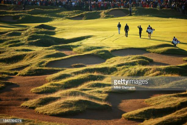 Dustin Johnson of team United States and Collin Morikawa of team United States walk down the first hole during Friday Morning Foursome Matches of the...