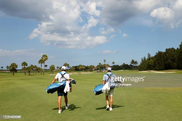 Dustin Johnson of the American Nurses Foundation team and Rory McIlroy of the American Nurses Foundation team carry their bags during the TaylorMade...