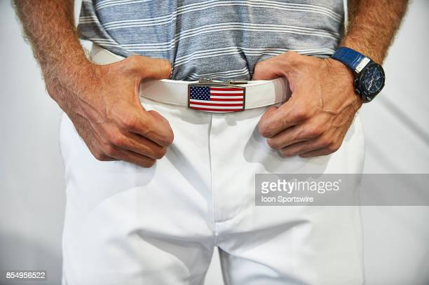 Dustin Johnson of the American Team shows his American Flag belt buckle after practice rounds prior to the Presidents Cup at Liberty National Golf...