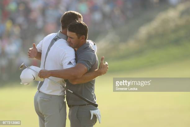 Dustin Johnson of the United States and Brooks Koepka of the United States hug on the 18th green during the final round of the 2018 US Open at...
