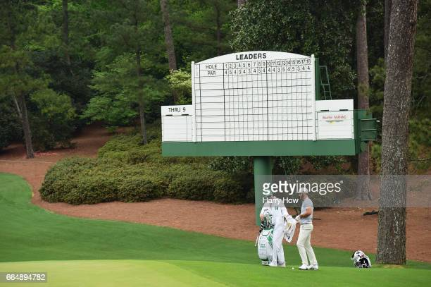 Dustin Johnson of the United States and caddie Austin Johnson on the tenth green during a practice round prior to the start of the 2017 Masters...