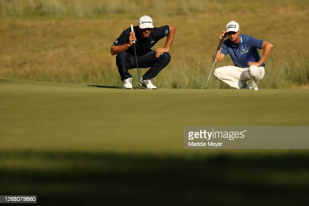 Dustin Johnson of the United States and Harris English of the United States lines up a putt on the 12th green during the final round of The Northern...