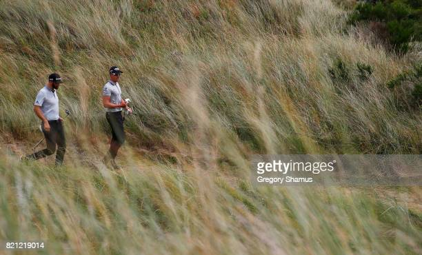 Dustin Johnson of the United States and Henrik Stenson of Sweden walk together during the final round of the 146th Open Championship at Royal...