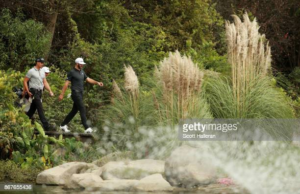 Dustin Johnson of the United States and Henrik Stenson of Sweden walk from the 8th tee during the final round of the WGC HSBC Champions at Sheshan...
