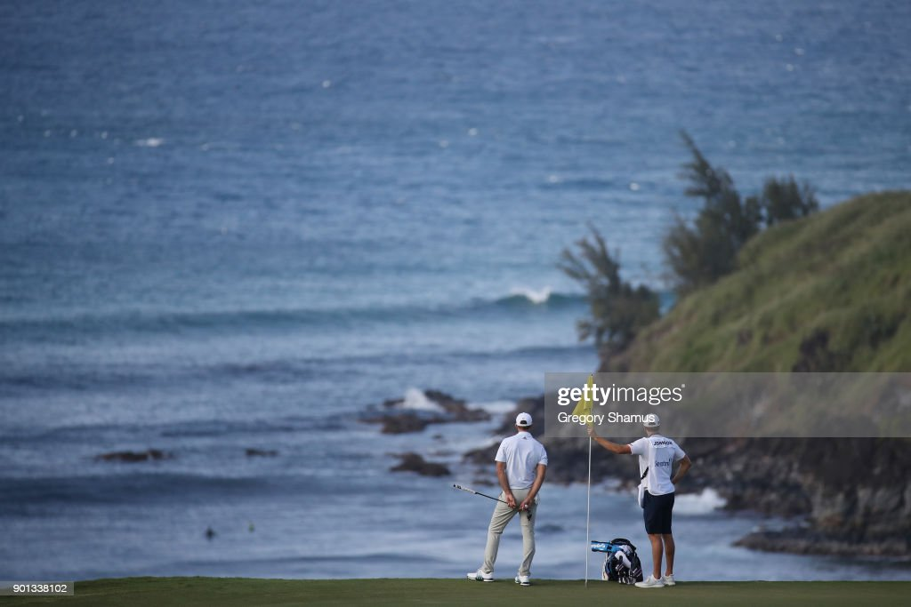 Dustin Johnson of the United States and his caddie and brother Austin Johnson look on from the 11th green over Honolua Bay during the first round of the Sentry Tournament of Champions at Plantation Course at Kapalua Golf Club on January 4, 2018 in Lahaina, Hawaii.