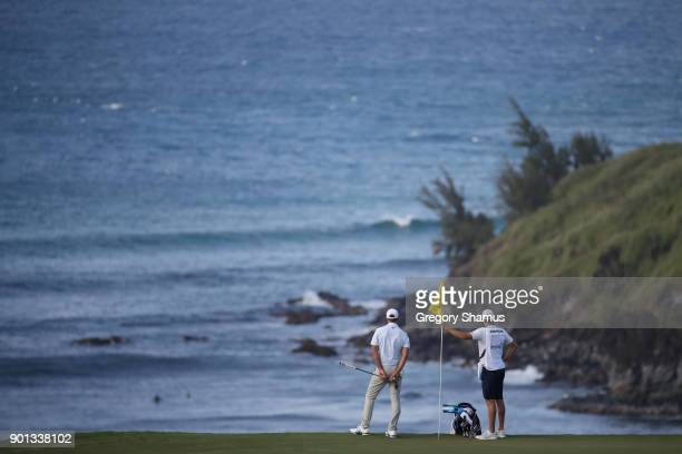 Dustin Johnson of the United States and his caddie and brother Austin Johnson look on from the 11th green over Honolua Bay during the first round of...