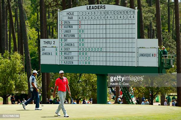 Dustin Johnson of the United States and Jason Day of Australia walk on the third green during the final round of the 2016 Masters Tournament at...