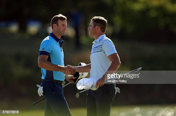 Dustin Johnson of the United States and Luke List of the United States shakes hands after finishing their round on the 18th green during the third...