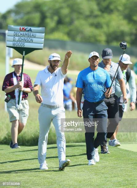 Dustin Johnson of the United States and Tiger Woods of the United States walk up the eighth hole during a practice round prior to the 2018 US Open at...