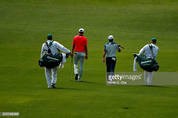 Dustin Johnson of the United States caddie Austin Johnson Jason Day of Australia and caddie Colin Swatton walk on the fourth hole during the final...