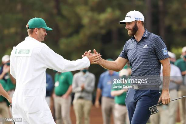Dustin Johnson of the United States celebrates with caddie Austin Johnson on the 18th green after winning the Masters at Augusta National Golf Club...