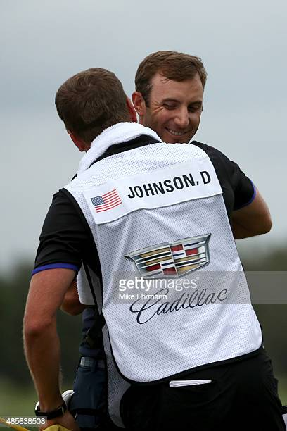 Dustin Johnson of the United States celebrates with caddie Austin Johnson on the eighteenth hole green after winning the World Golf...