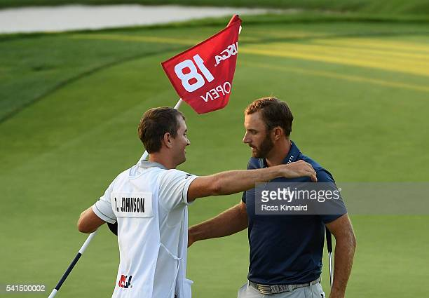 Dustin Johnson of the United States celebrates with caddie Austin Johnson after winning the US Open at Oakmont Country Club on June 19 2016 in...