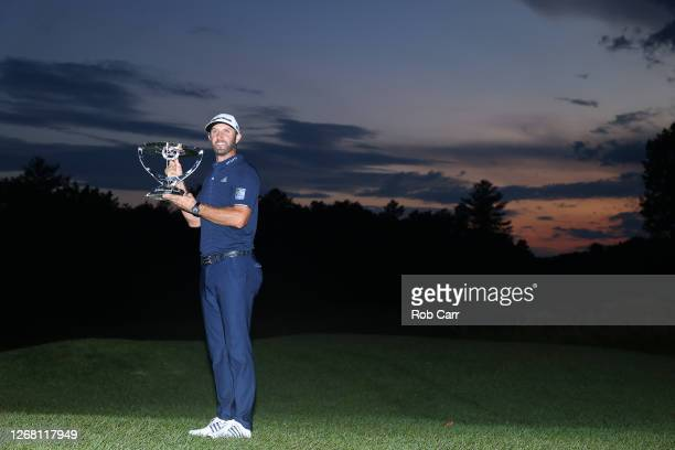 Dustin Johnson of the United States celebrates with the trophy after going 30-under par to win during the final round of The Northern Trust at TPC...