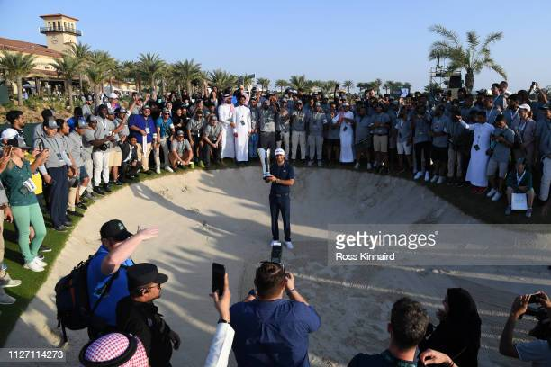 Dustin Johnson of The United States celebrates with the trophy and the volunteers during Day four of the Saudi International at the Royal Greens Golf...