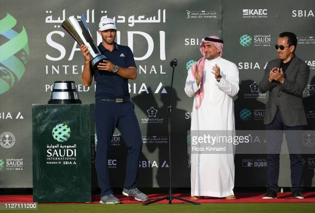 Dustin Johnson of The United States celebrates with the trophy next to His Excellency Yasir AlRumayyan and Saleh Romeih during Day four of the Saudi...