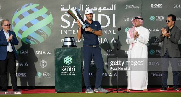 Dustin Johnson of The United States celebrates with the trophy next to His Excellency Yasir Al-Rumayyan and Majed Al Sorour, CEO of the Saudi Golf...