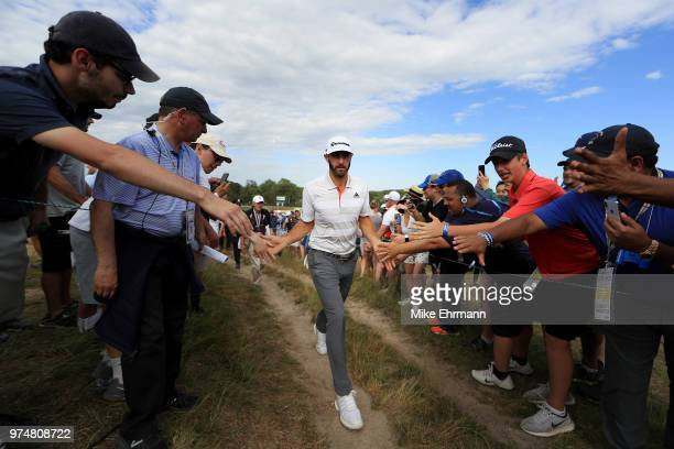Dustin Johnson of the United States greets fans as he walks off a green during the first round of the 2018 US Open at Shinnecock Hills Golf Club on...