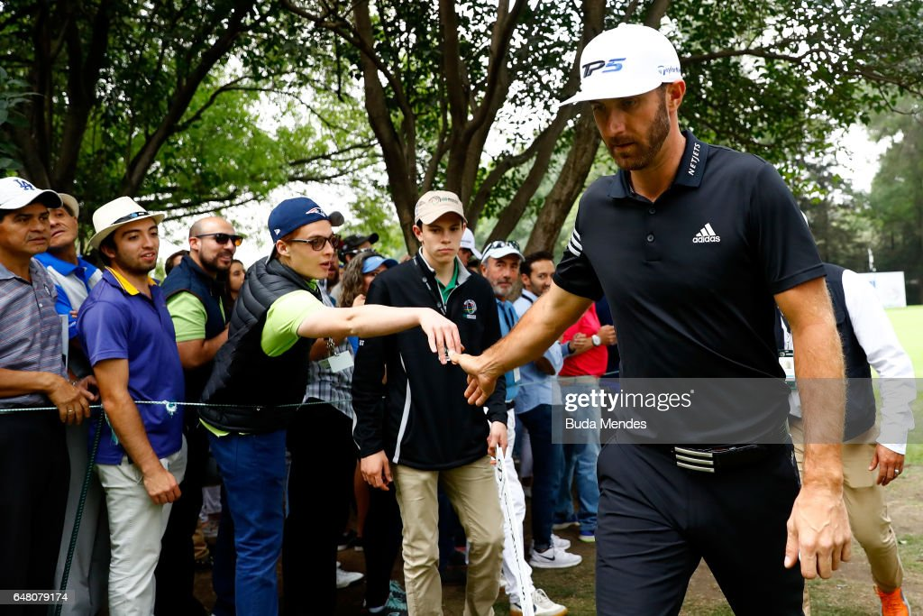 Dustin Johnson of the United States high-fives fans on the ninth hole during the third round of the World Golf Championships Mexico Championship at Club De Golf Chapultepec on March 4, 2017 in Mexico City, Mexico.