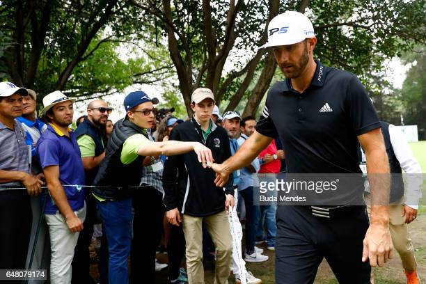 Dustin Johnson of the United States highfives fans on the ninth hole during the third round of the World Golf Championships Mexico Championship at...