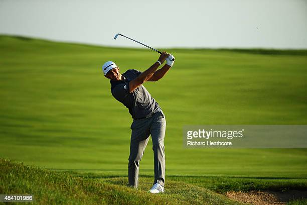 Dustin Johnson of the United States hits his second shot on the 16th hole during the continuation of the weather-delayed second round of the 2015 PGA...