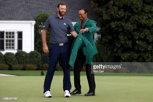 Dustin Johnson of the United States is awarded the Green Jacket by 2019 Masters champion Tiger Woods of the United States during the Green Jacket...