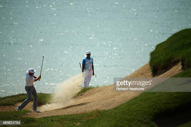 Dustin Johnson of the United States plays a bunker shot on the third hole as Rickie Fowler looks on during the first round of the 2015 PGA...