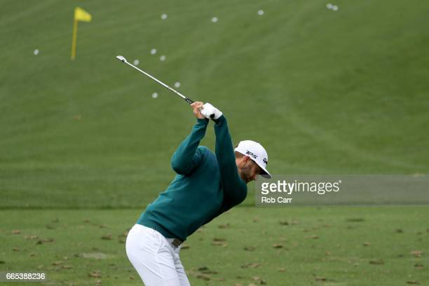 Dustin Johnson of the United States plays a shot on the practice range prior to withdrawing during the first round of the 2017 Masters Tournament at...