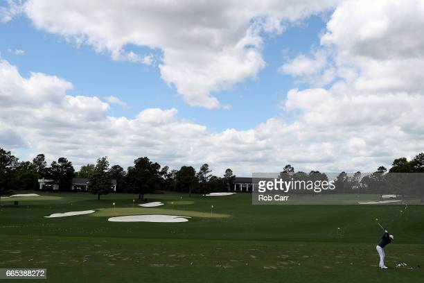 Dustin Johnson of the United States plays a shot on the practice range prior to announcing his withdrawl during the first round of the 2017 Masters...