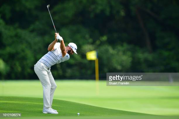 Dustin Johnson of the United States plays an approach shot during a practice round prior to the 2018 PGA Championship at Bellerive Country Club on...