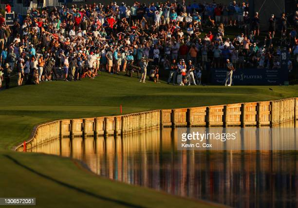 Dustin Johnson of the United States plays his shot from the 18th tee as fans look on during the first round of THE PLAYERS Championship on THE...