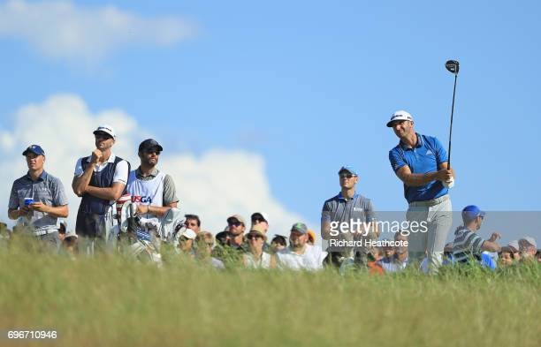 Dustin Johnson of the United States plays his shot from the tenth tee as Jordan Spieth of the United States and Martin Kaymer of Germany look on...