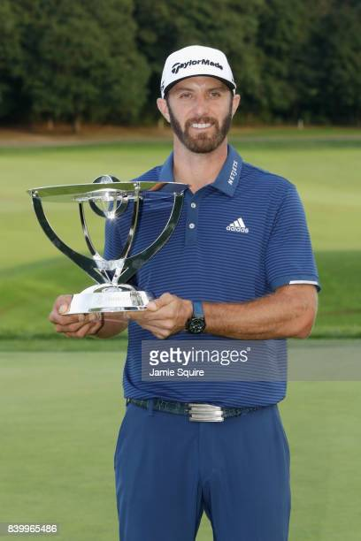 Dustin Johnson of the United States poses with the trophy after putting for birdie on the 18th green to defeat Jordan Spieth of the United States in...
