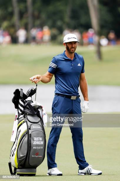 Dustin Johnson of the United States pulls a club from his bag as he prepares to play a shot on the seventh hole during the third round of THE PLAYERS...