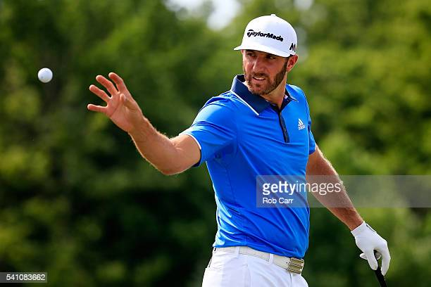 Dustin Johnson of the United States reaches for a golf ball on the practice ground during the third round of the US Open at Oakmont Country Club on...