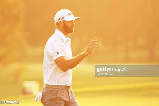 Dustin Johnson of the United States reacts after making a par putt on the 18th green during the third round of the Masters at Augusta National Golf...