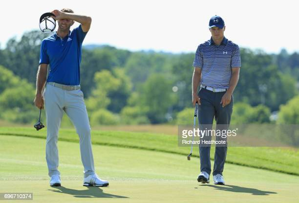 Dustin Johnson of the United States reacts on the eighth green as Jordan Spieth of the United States looks on during the second round of the 2017...