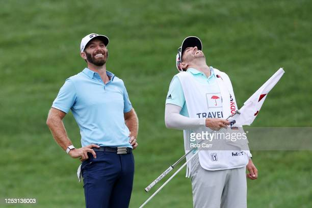 Dustin Johnson of the United States reacts with caddie Austin Johnson after making a putt for par on the 18th green to win the Travelers Championship...