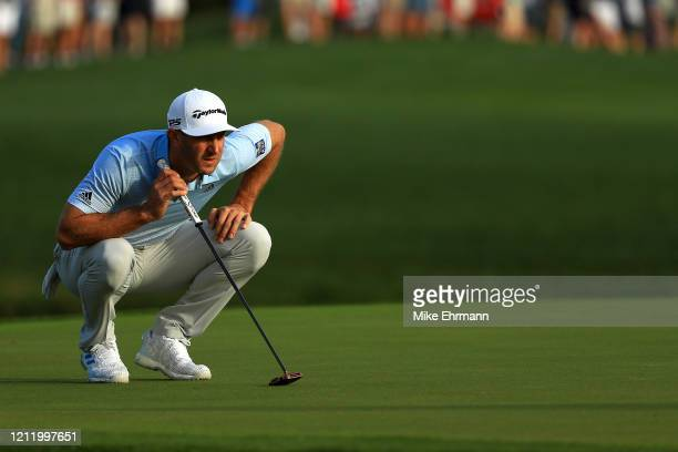 Dustin Johnson of the United States reads a putt on the 11th green during the first round of The PLAYERS Championship on The Stadium Course at TPC...
