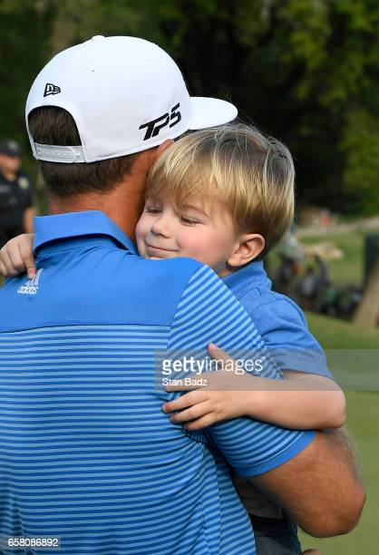 Dustin Johnson of the United States receives a victory hug from his son Tatum on the 18th green after winning the championship match at the World...