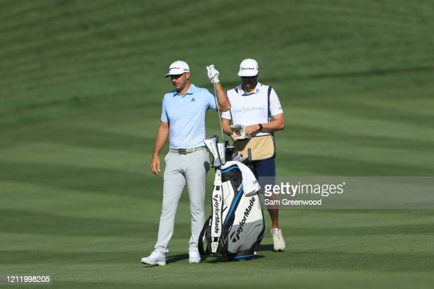 Dustin Johnson of the United States selects a club on the 16th hole during the first round of The PLAYERS Championship on The Stadium Course at TPC...