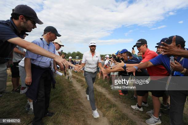 Dustin Johnson of the United States shakes hands with fans on his way to the 13th tee during the first round of the 2018 US Open at Shinnecock Hills...